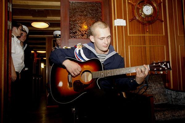 Курсант Алексей Безуглов исполняет песню для гостей парусника
